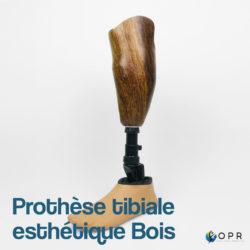 prothèse tibiale de jambe en carbone avec esthétique en bois des motifs u-exist realisé par les prothésistes en bretagne a rennes et en normandie a avranches et saint lo