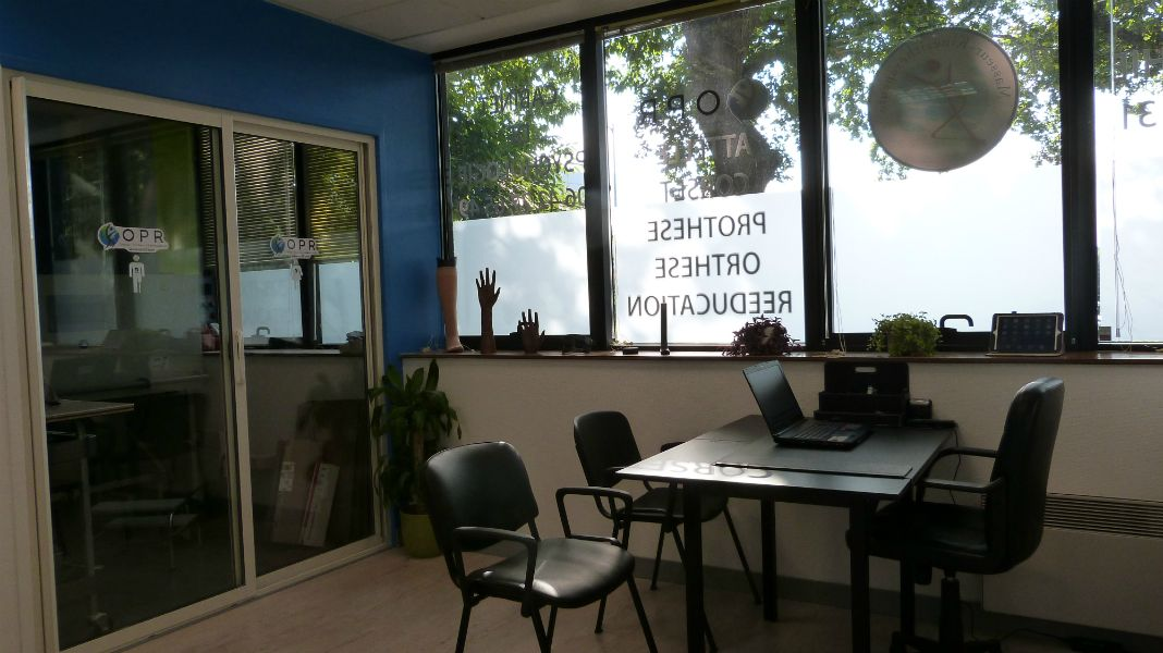Salle orthoprothésiste avec l'atelier derrière les baies vitrées